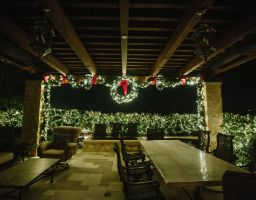 garland and wreaths hung over patio with warm white LED lights