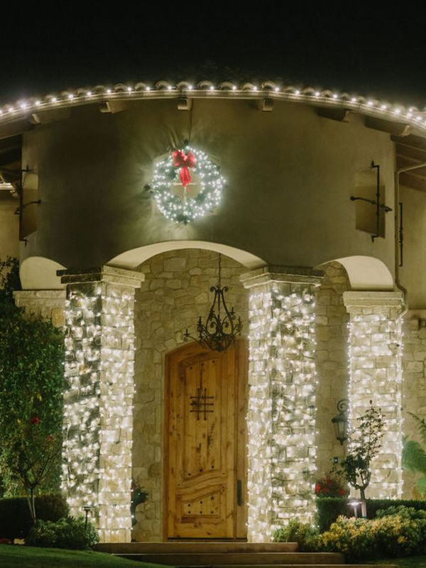 front of house and columns lit with christmas lights and wreath